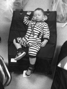 Trøtt gutt, slapper av på Bugaboo travelbag hvor vognen hans er inni
