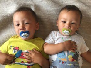 To storebrødre poserer med bittelillebror sine nye navnesmokker 🍼