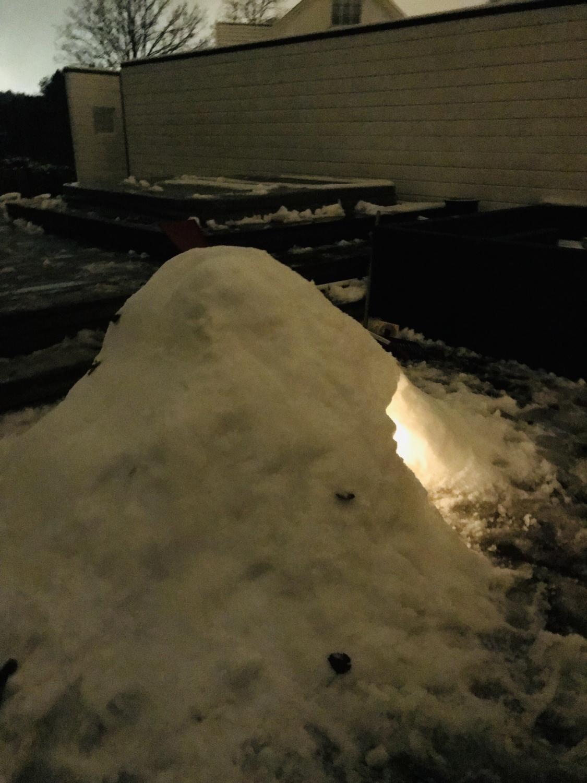 Snøhule med lys inni lyser opp verandaen